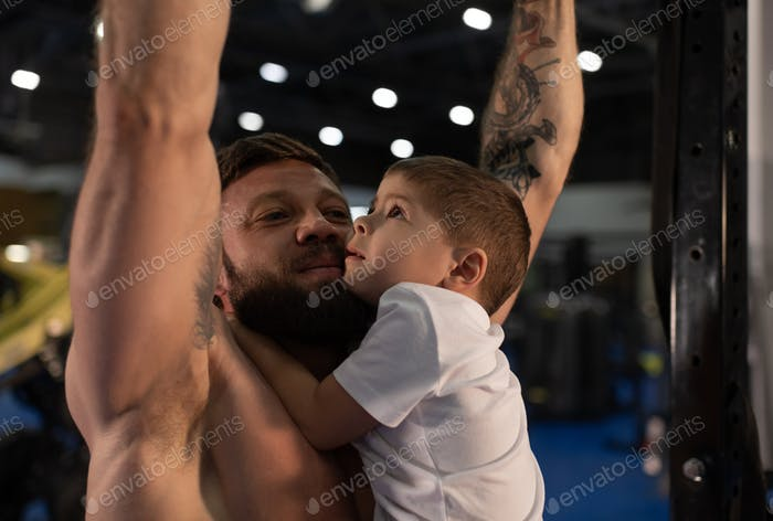 Strong father doing pull ups with son