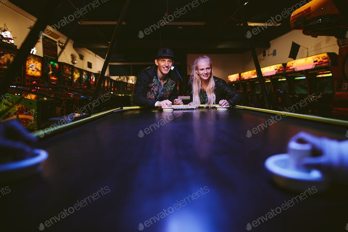 Friends playing a game of air hockey