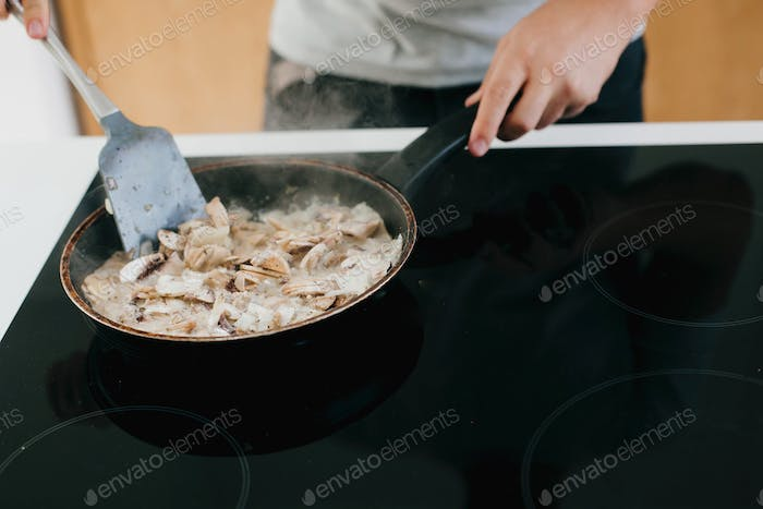 Person roasting mushrooms and onion on electric stove