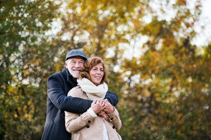 Senior couple standing in an autumn nature, hugging.
