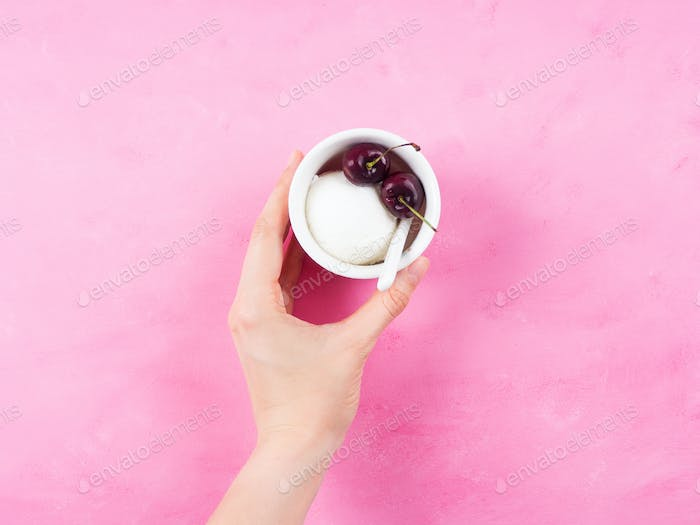 Frozen yogurt dessert in cup in female hand