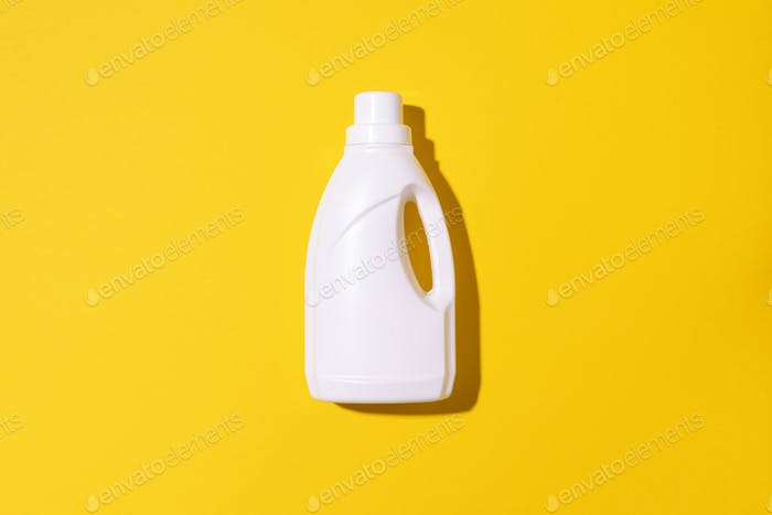 White plastic bottle of cleaning product, household chemicals or liquid laundry detergent on yellow