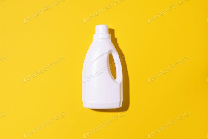 Weiße Plastikflasche mit Reinigungsmitteln, Haushaltschemikalien oder flüssigem Waschmittel auf gelb