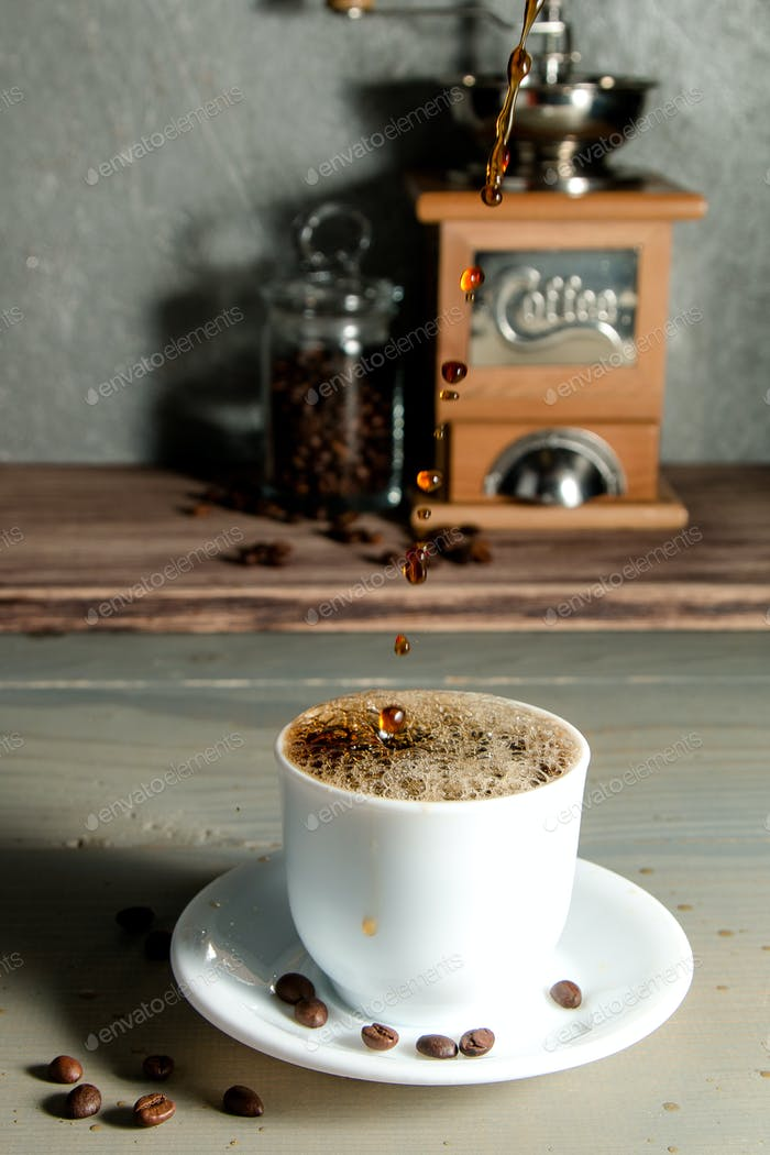 Pouring a Cup of Coffee Creating Splash on Wooden Background.