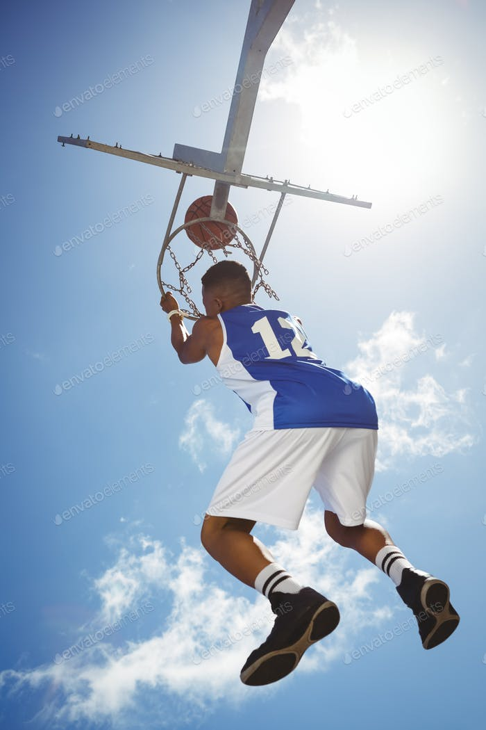 Rear view of male teenager hanging on basketball hoop