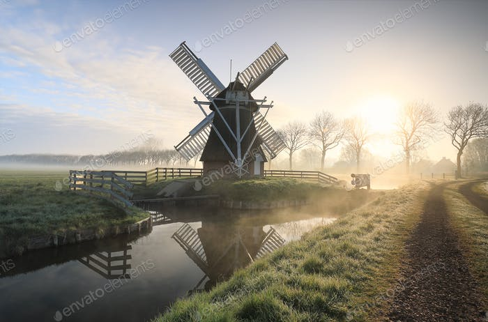 windmill in fog by river and road