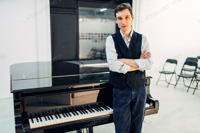 Male pianist stands at the black grand piano