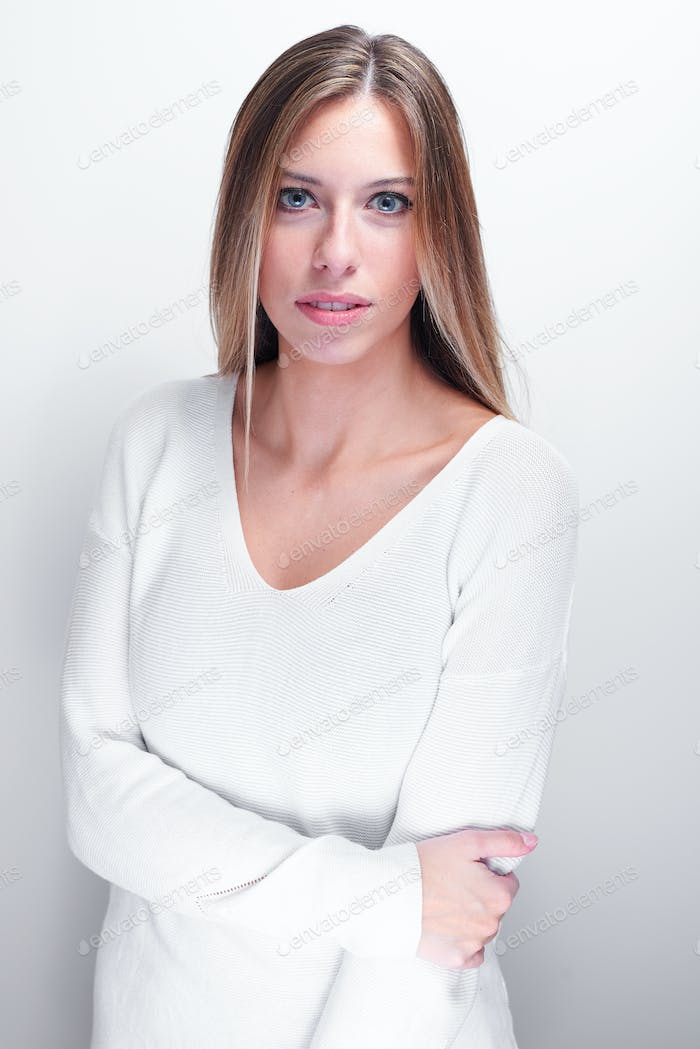 Shy woman looking at camera on a white background
