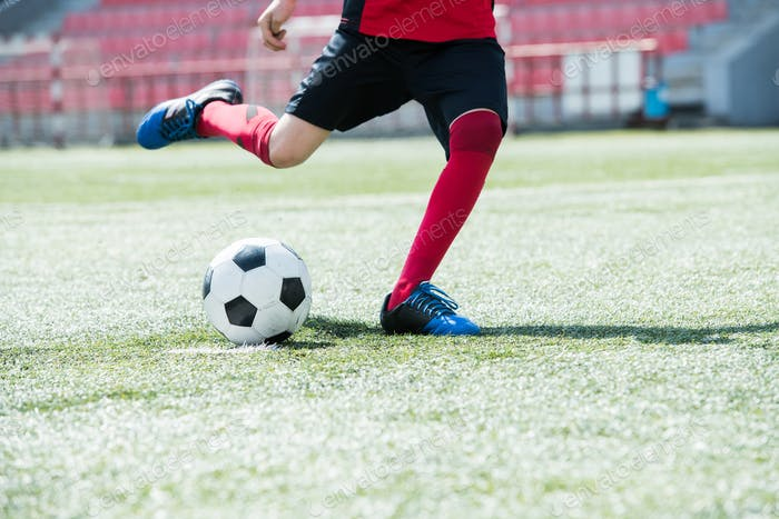 Young Football Player Kicking Ball