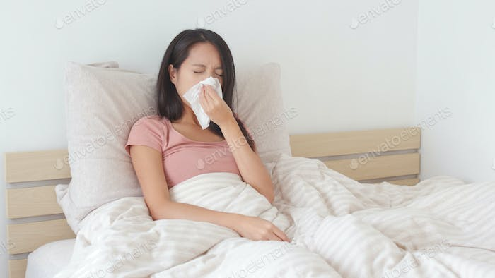 Woman getting sick and sneezing on bed