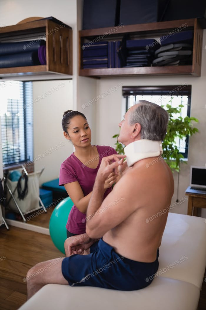 Female therapist examining neck collar of senior male patient sitting on bed
