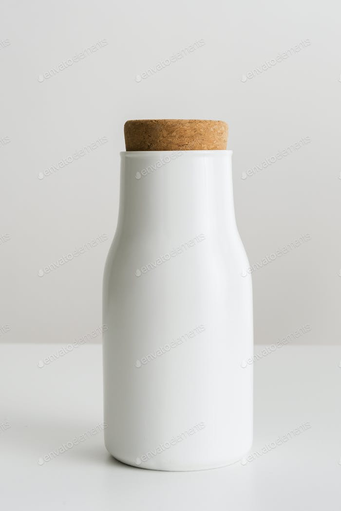 Minimal white metal container sealed with a cork