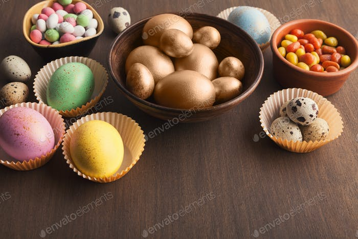 Colourful eggs and candies on dark background