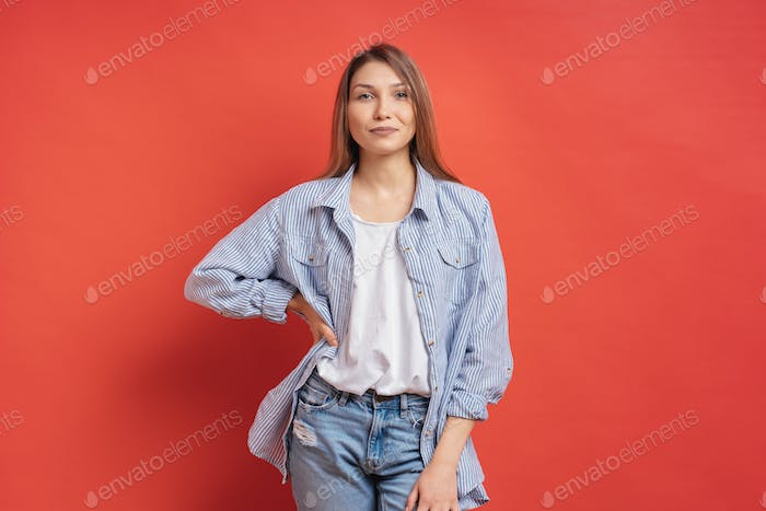 Pretty female model posing with a smiling face expression on red background
