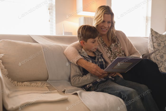 Mother with her son spending time together while reading a story book in living room at home
