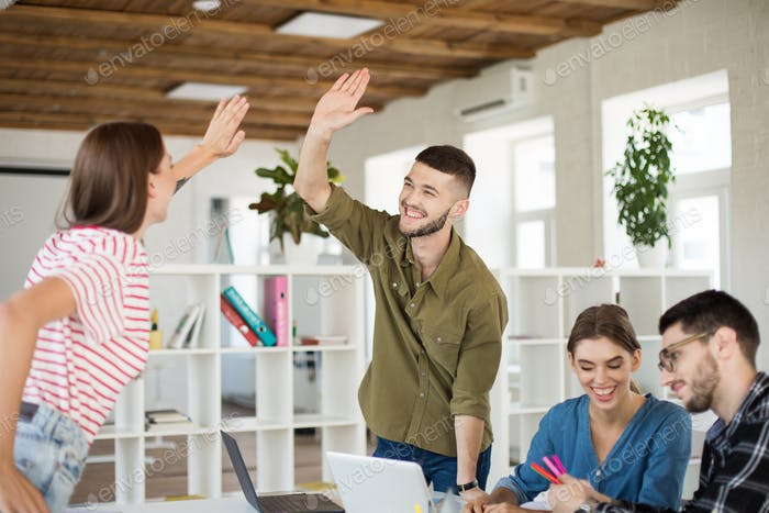 Young joyful man in shirt happily giving  high five to colleague
