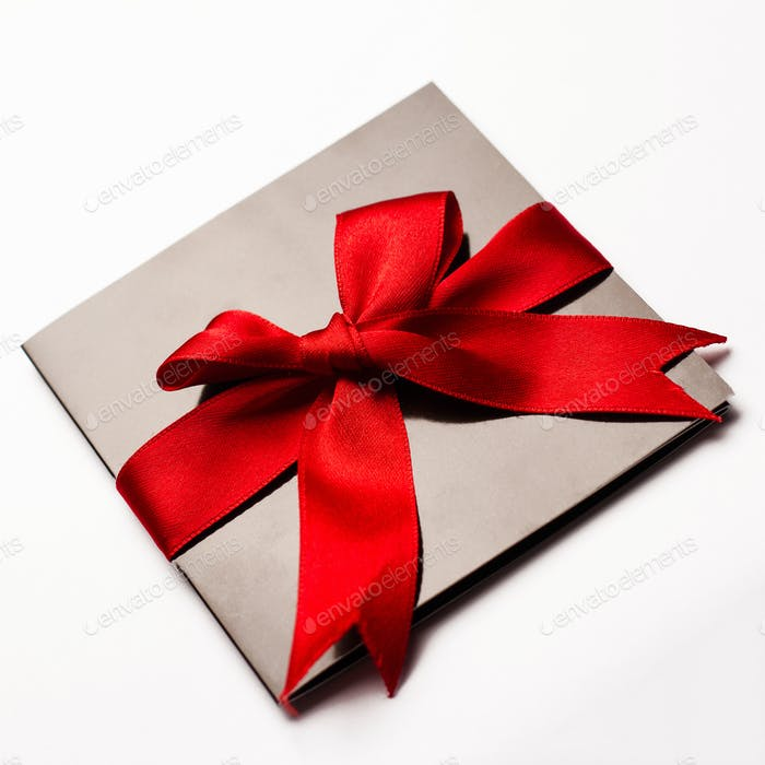Black paper card with red textile ribbon isolated on white