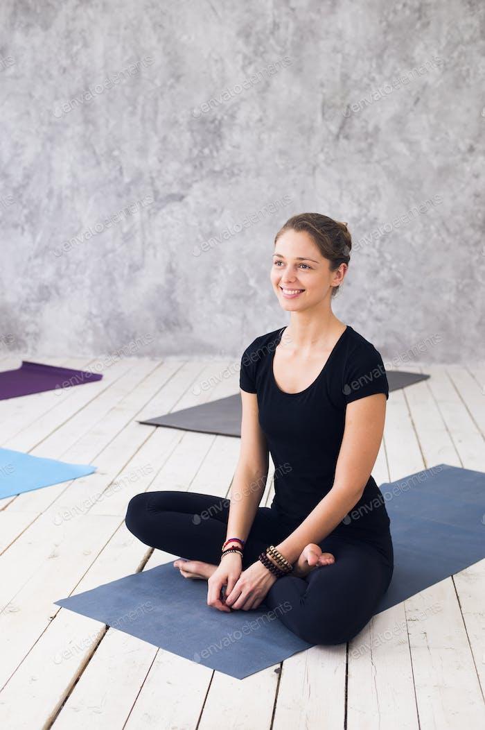Junge attraktive Frau praktiziert Yoga, sitzt in Ardha Padmasana Übung, Half Lotus Pose