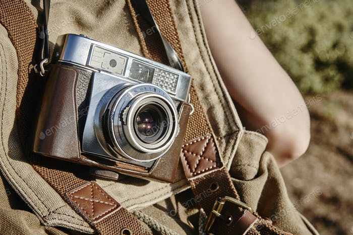 Carrying a vintage camera on the countryside. Film photography