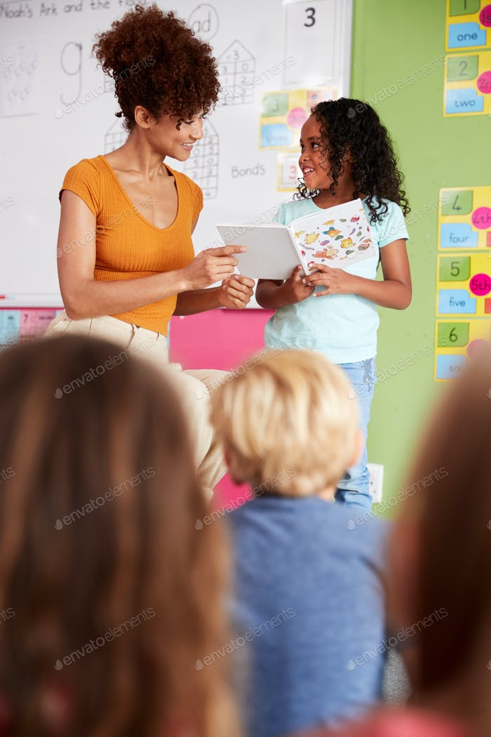 Female Pupil In Elementary School Classroom Reading Book To Class With Teacher