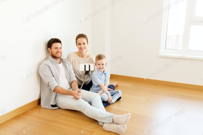 family taking selfie by smartphone at new home