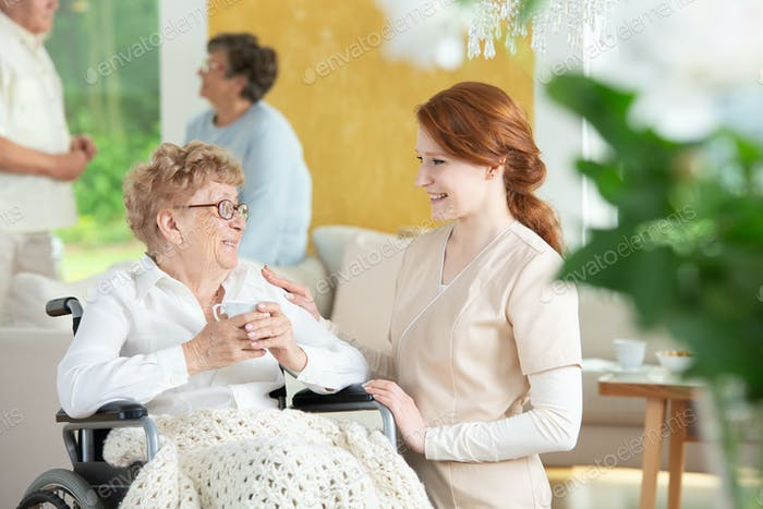 Happy nurse talking with smiling paralysed elderly woman in the