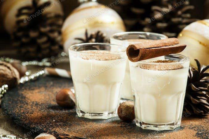 Eierpunsch mit Milch, Zimt, geriebener Muskatnuss, verziert mit Tannenzapfen, Perlen, Nüssen