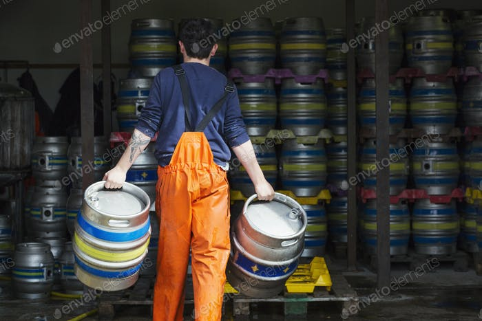 Rear view of man working in a brewery, carrying a metal beer keg in either hand.