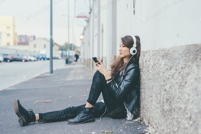 Young beautiful asiatic woman sitting on the floor listening to music