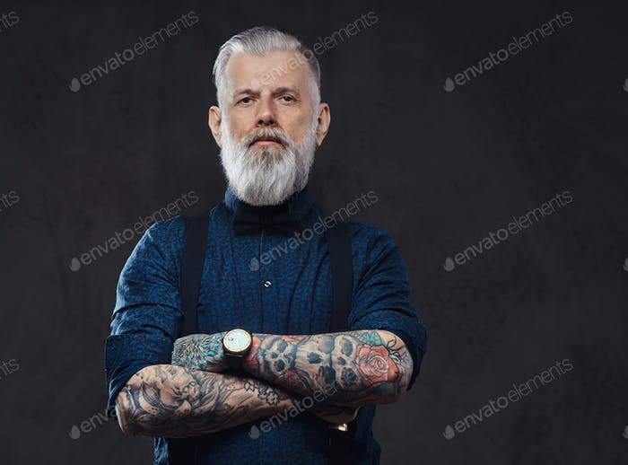 Caucasian grandfather poses in dark background with crossed arms