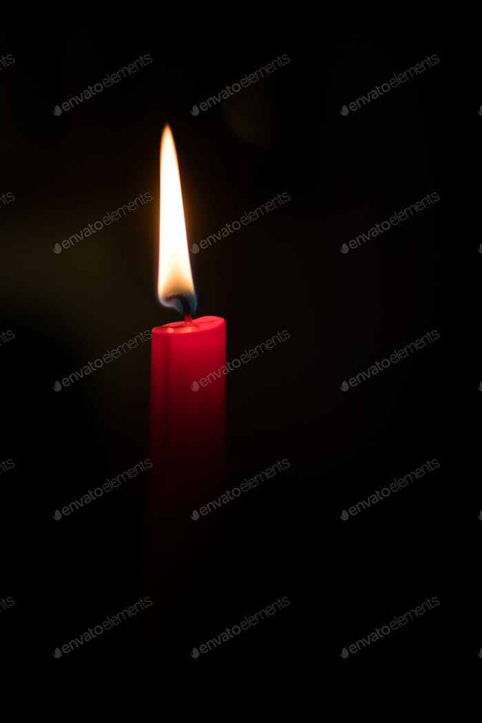Single burning candle in the dark