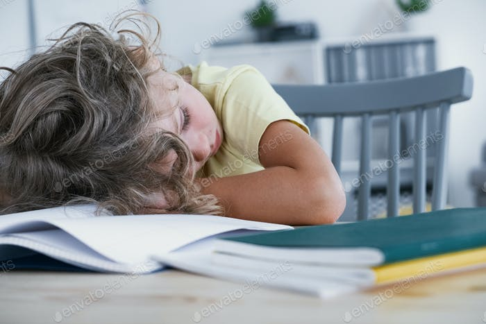 Close-up of a tired kid sleeping with his head rested on a table