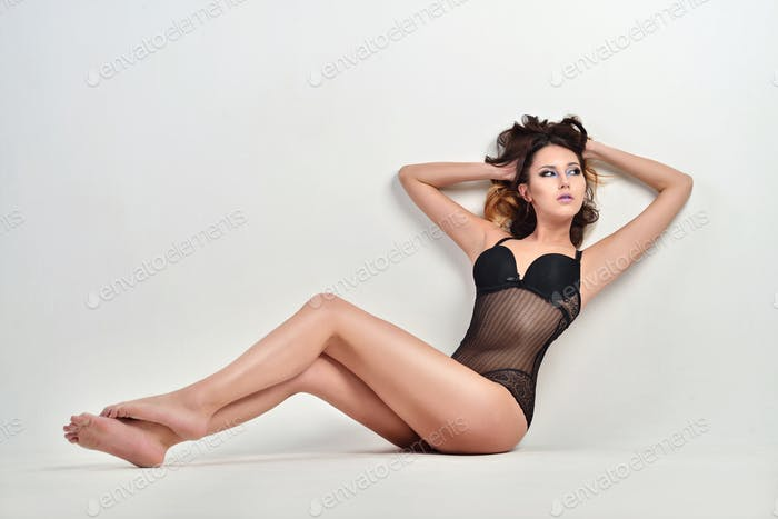 Beautiful sexy lady in elegant bodysuit isolated on a white background