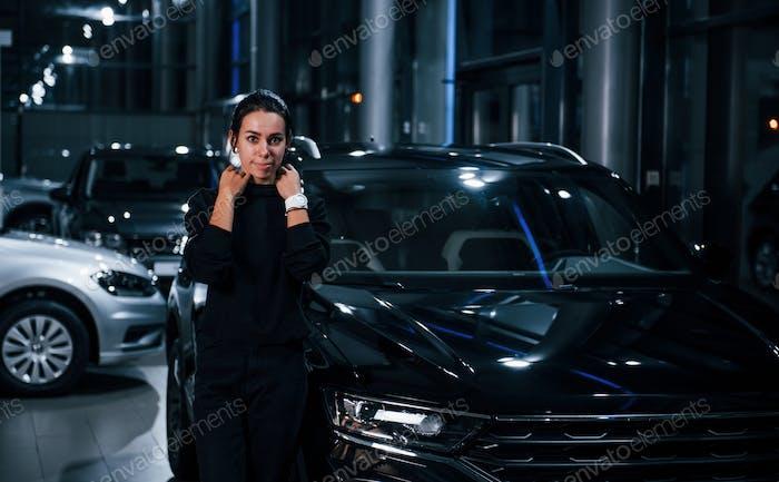 Brünette steht in der Nähe von schwarz gefärbten Autos und lächelt