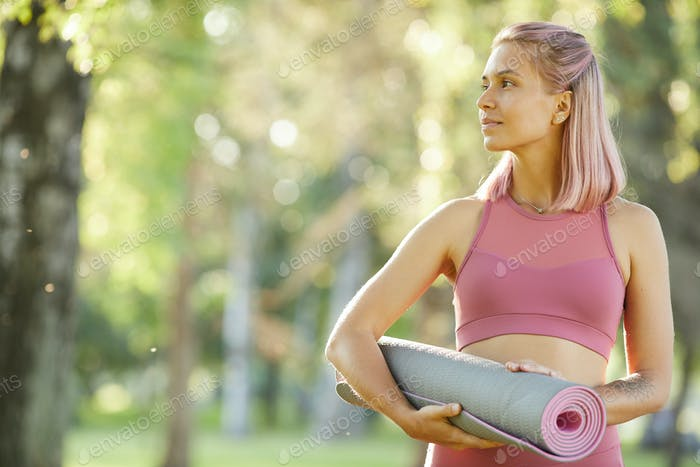 Woman with exercise mat outdoors
