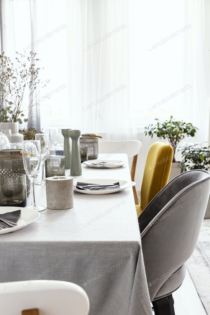 Real photo of table with dinnerware, candle and grey and yellow