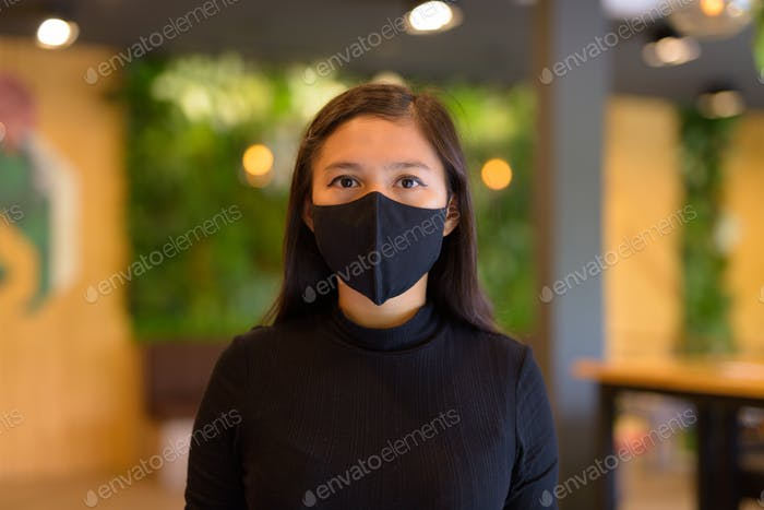 Face of young Asian businesswoman wearing mask and social distancing at the coffee shop