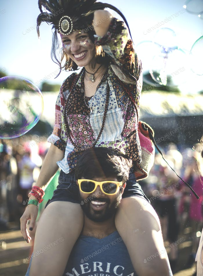 Revellers at a summer music festival young man wearing yellow sunglasses carrying woman wearing
