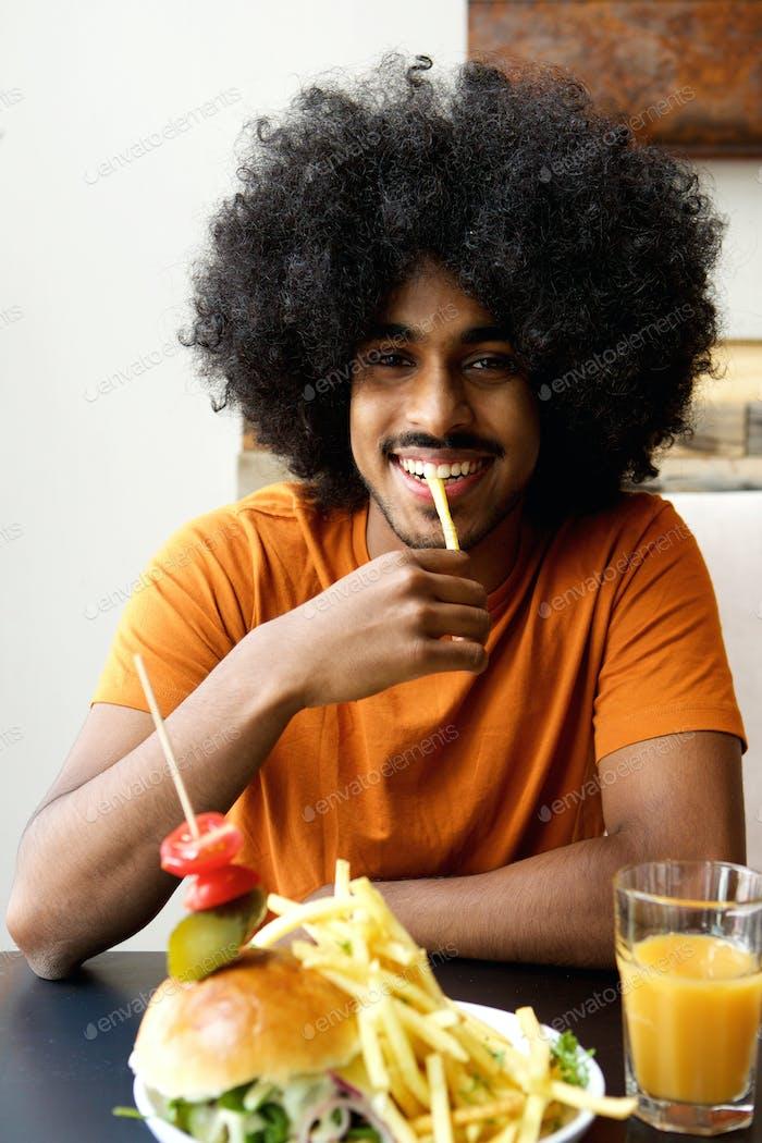 Young black man eating fries at restaurant