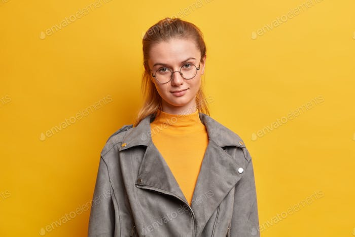 Isolated shot of pretty serious female wears round spectacles looks directly at camera with calm exp