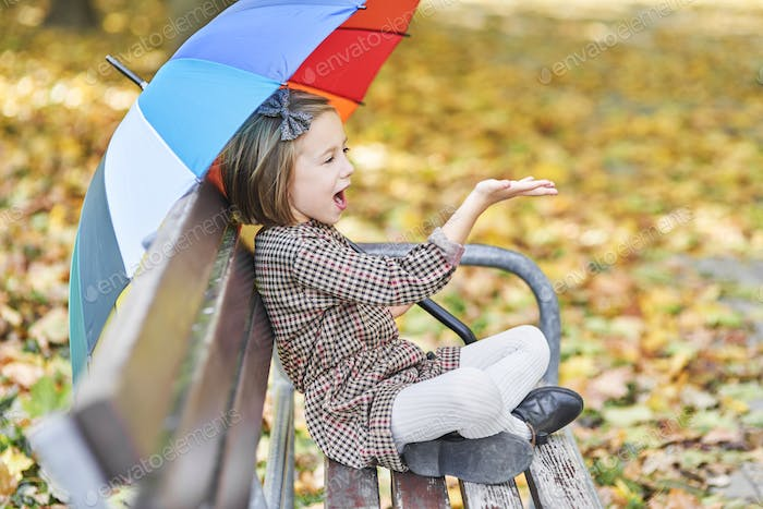 Girl looking for shelter with umbrella