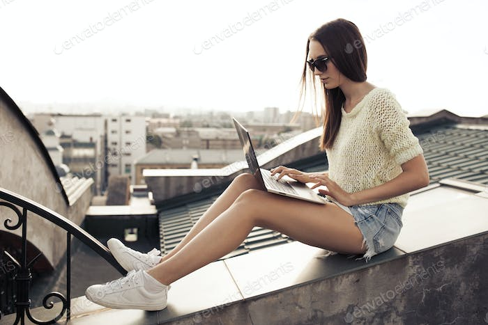 Side View Of A Young Woman Using Laptop At House Roof