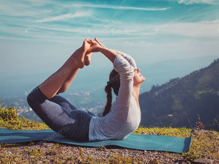 woman doing Ashtanga Vinyasa Yoga asana Dhanurasana - bow pose