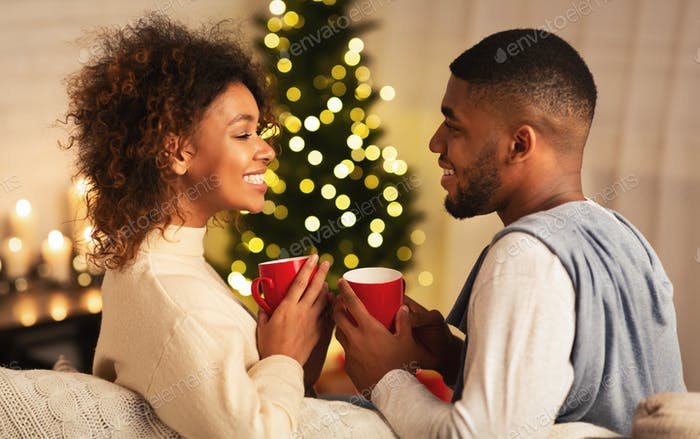 Excited black couple drinking coffee on Christmas eve