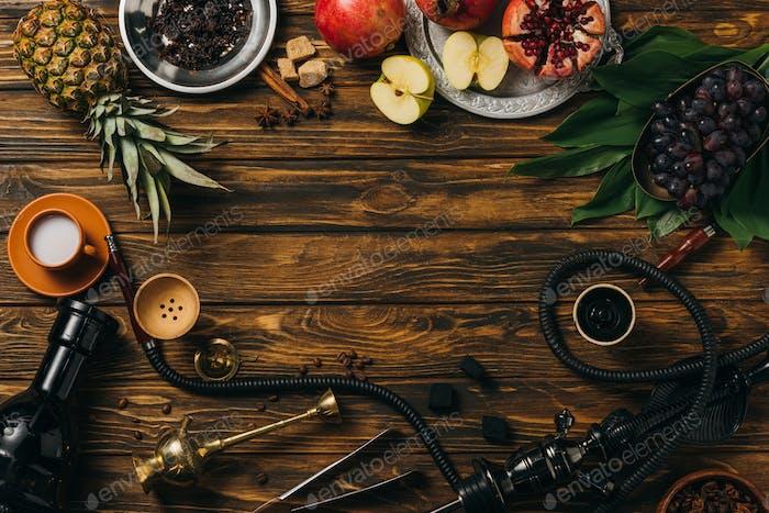 Draufsicht auf Tabak, Shisha, Kohlen, Zimt, Tasse Milch und exotische Früchte auf Holzoberfläche