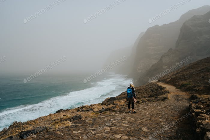 Santo Antao, Cape Verde - Female hiker on trail hike Cruzinha da Garca to Ponta do Sol. Moody