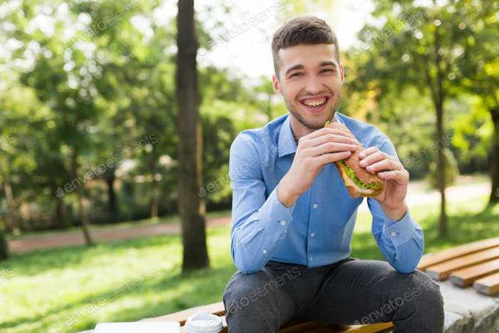 Young laughing man in blue shirt sitting on bench with sandwich