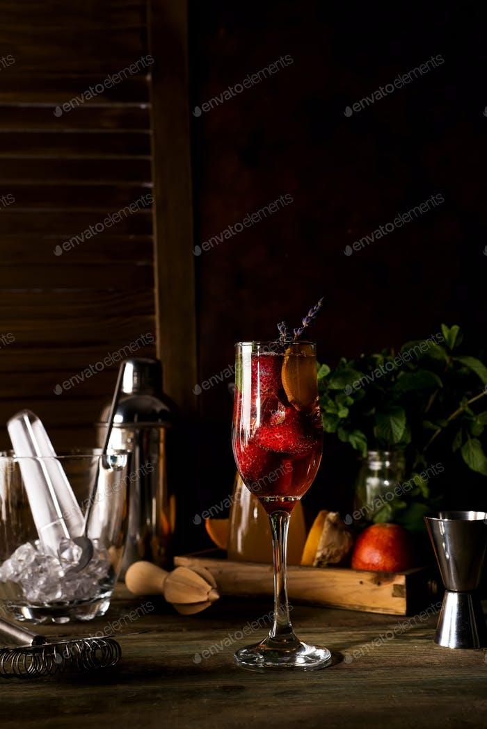 Champagne with slices of strawberry and lavender twigs on dark wooden backgorund