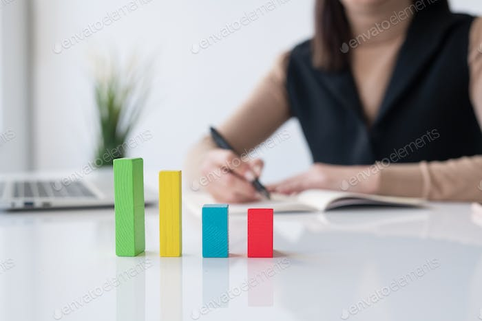 Multi-color cube chart on desk on background of accountant or broker