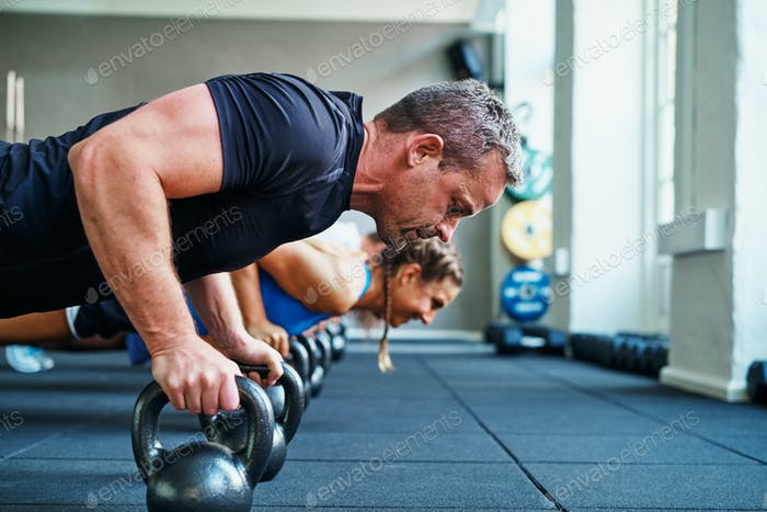 Focused man doing pushups on weights in a gym class